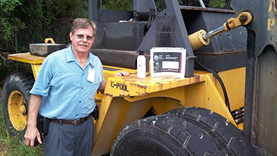 Image of a guy with lubricants and a large construction vehicle.